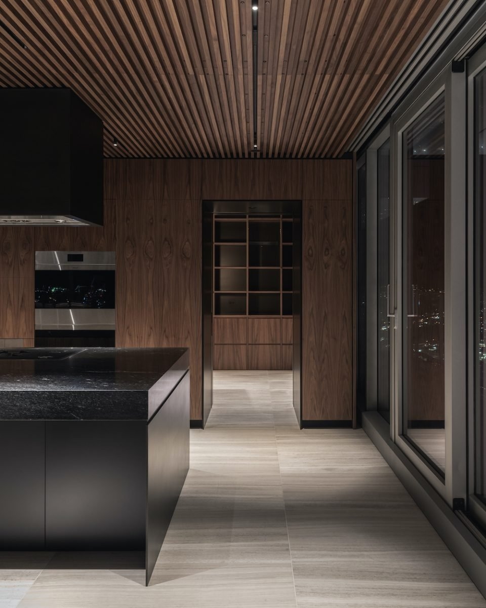 The kitchen walls and ceiling are clad in custom millwork